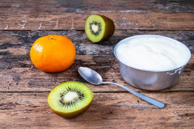 Iogurte natural e frutas na mesa de madeira