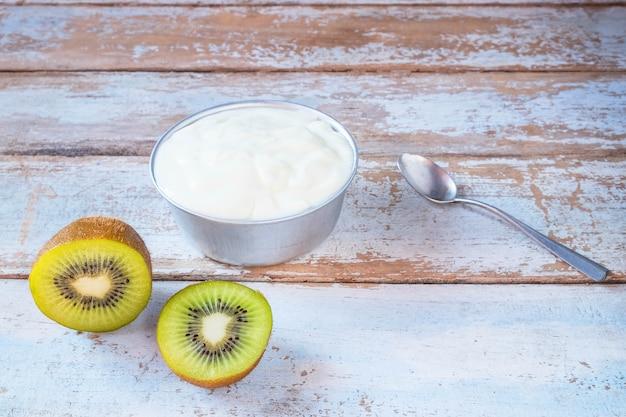 Iogurte natural e kiwis na mesa de madeira