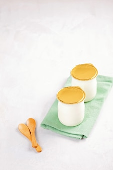 Iogurte natural industrial em latas de plástico. conceito de pequeno-almoço saudável e rápido