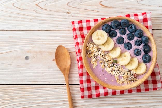 Iogurte ou tigela de smoothie de iogurte com baga azul, banana e granola - estilo de comida saudável