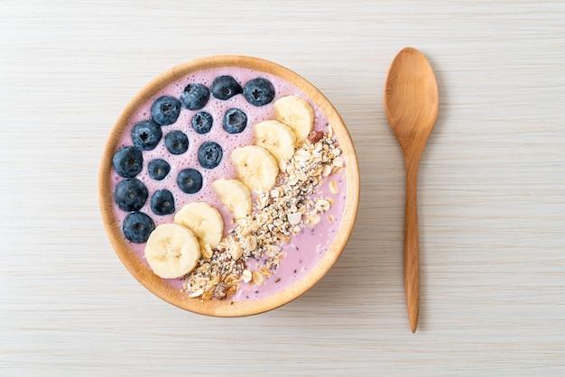 Iogurte ou tigela de suco de iogurte com baga azul, banana e granola. estilo de comida saudável