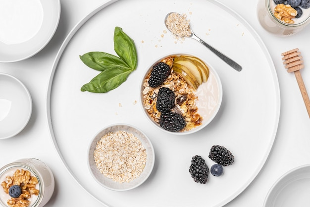 Iogurte plano leigo com aveia, frutas e mel no prato