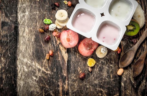 Iogurtes frescos com frutas e nozes. sobre um fundo de madeira.