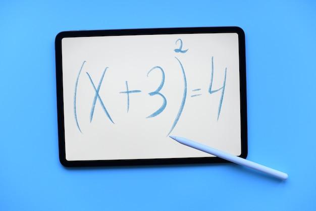 Ipad tablet com a inscrição da equação matemática com lápis maçã e sobre fundo azul