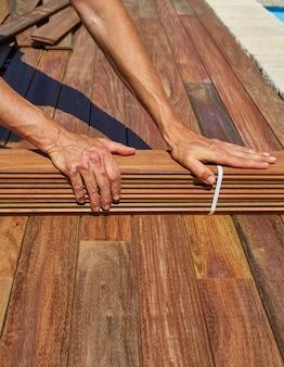 Ipe convés instalação carpinteiro mãos segurando madeira