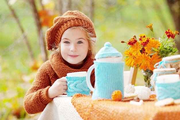 Irl que faz o tea party fora no jardim do outono. menina bebendo chá.