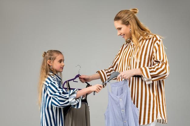 Irmã adulta sorridente, positiva, passando um tempo com sua filha e experimentando roupas bonitas