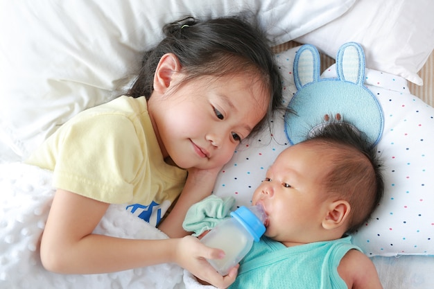 Irmã asiática bonito que alimenta o leite da garrafa para seu irmão e que encontra-se na cama.