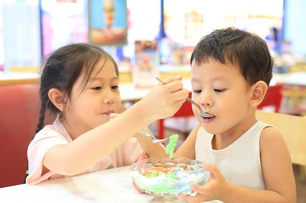 Irmã asiática e seu irmãozinho comendo sorvete juntos