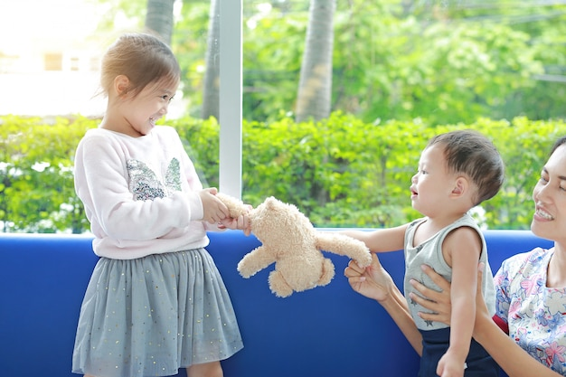 Irmã asiática que scrambling o urso de peluche com seu irmão mais novo.