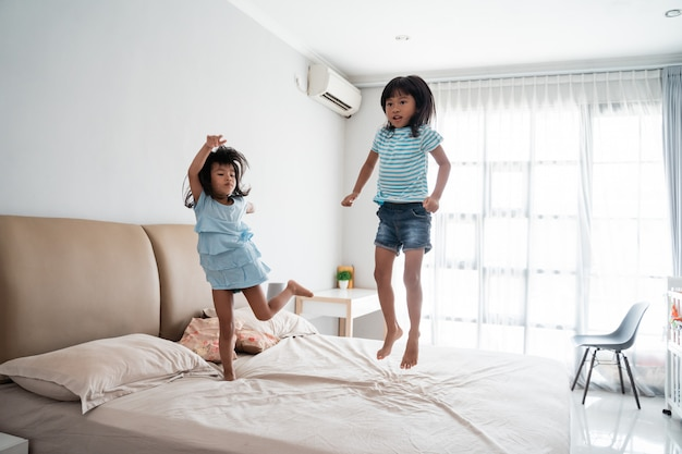 Irmã criança se divertindo pulando na cama
