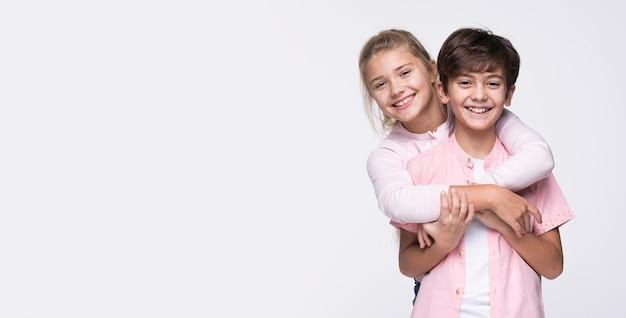 Irmã de cópia-espaço que abraça o irmão