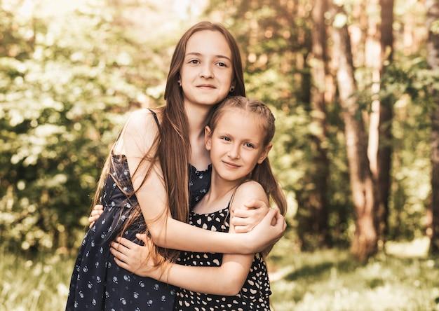 Irmã de duas meninas se abraçando e sorrindo para a natureza no verão