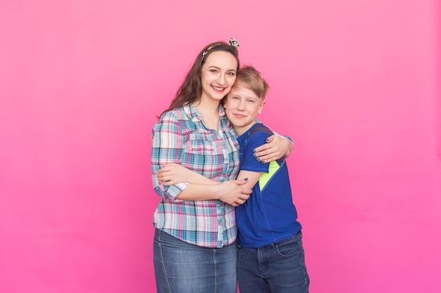 Irmã de retrato de família e irmão adolescente em fundo rosa