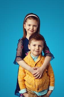 Irmã de vestido azul abraçando o irmão isolado sobre fundo azul