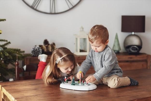 Irmã e irmão brincam com estatuetas de cerâmica para o natal