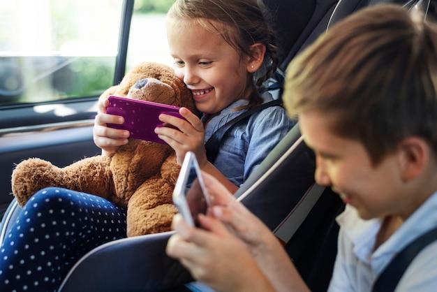 Irmã e irmão brincando com dispositivos digitais no carro