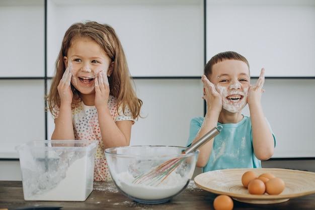 Irmã e irmão cozinhando juntos na cozinha