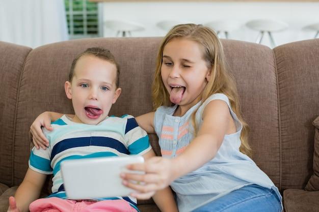 Irmã e irmão fazendo caretas engraçadas ao tirar selfie do celular
