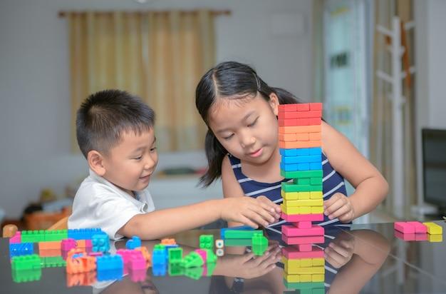 Irmã e irmão jogam tijolo de madeira,