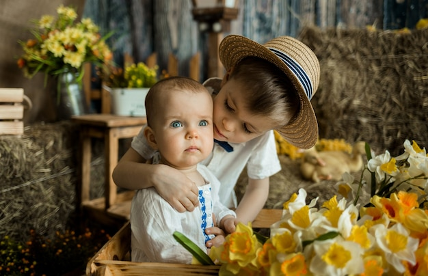 Irmã e irmão mais novo caucasianos se acariciam nas decorações da páscoa. páscoa para crianças