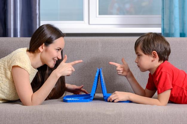 Irmã e irmão mais novo, jogam um jogo de guerra, deitam no sofá da sala e se olham nos olhos.