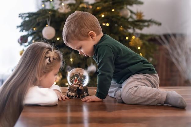 Irmã e irmão olhando para uma bola de vidro com uma cena do presépio de jesus cristo em uma bola de vidro em uma árvore de natal