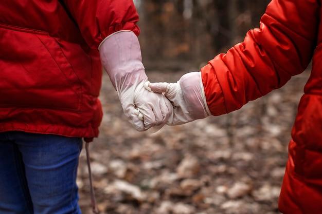 Irmã e irmão segurando de mãos dadas com luvas médicas durante a caminhada