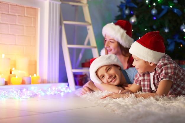 Irmã e irmãos felizes com presentes no chão em uma sala decorada de natal
