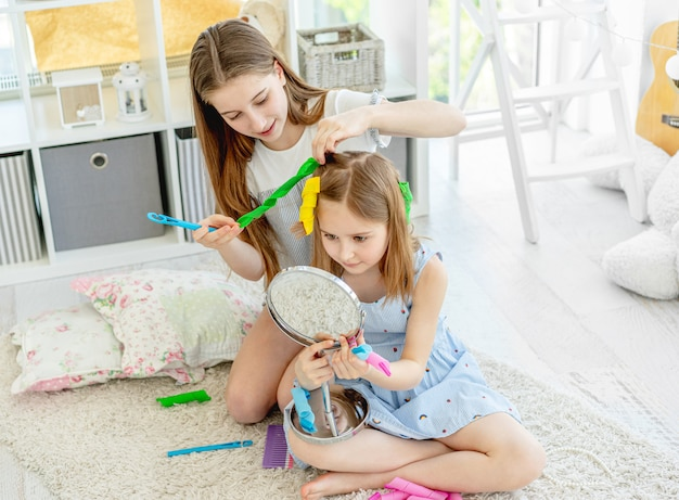 Irmã fazendo penteado para menina