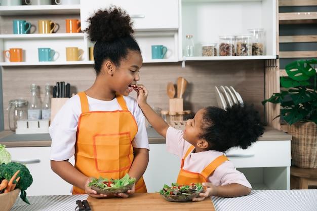 Irmã feliz com pele negra com salada no prato na cozinha