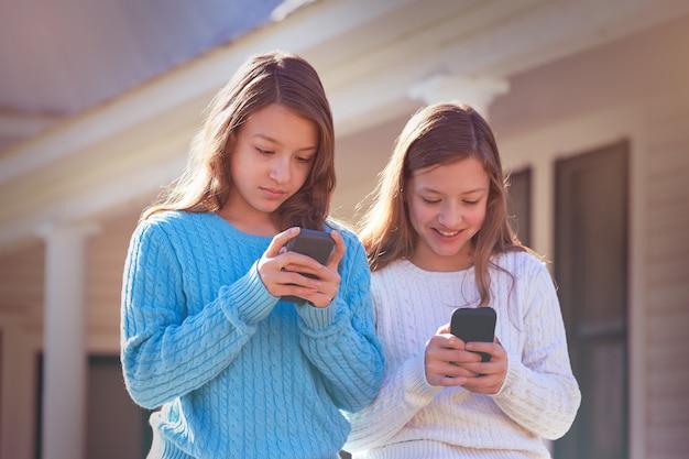Irmã gêmeos se divertindo com smartphone de tecnologia