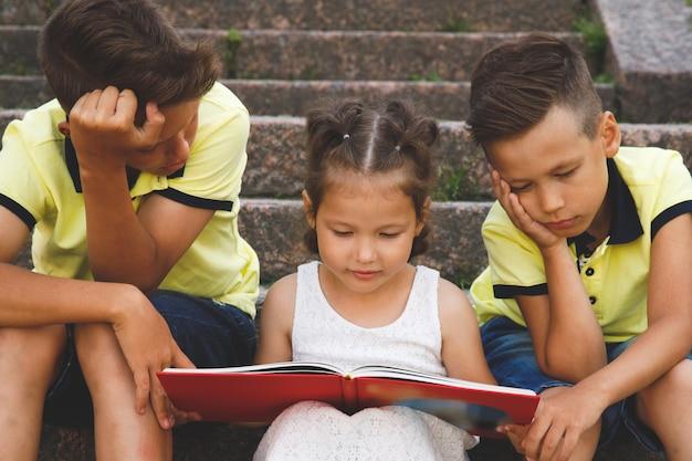 Irmã lê um livro para irmãos. eles estão entediados