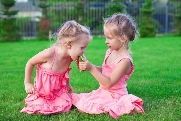 Irmã mais velha, alimentando um pedaço mais jovem de melancia em um dia quente de verão