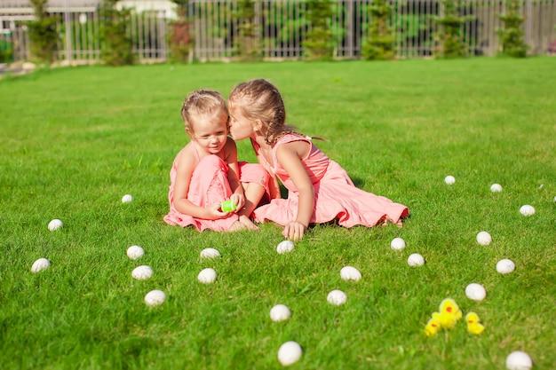Irmã mais velha beijando mais jovem em uma clareira verde de ovos de páscoa