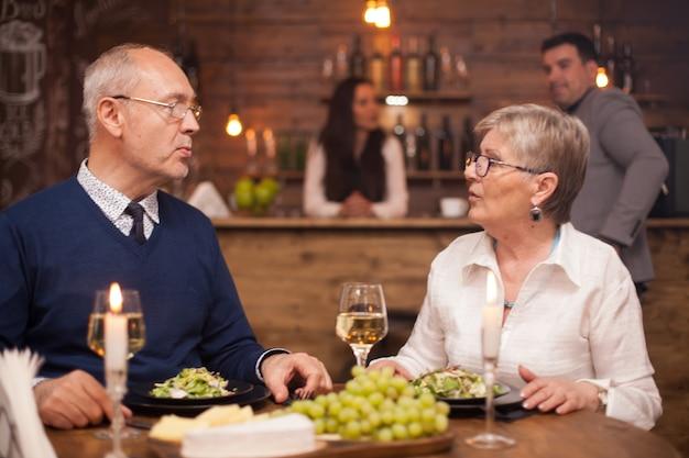 Irmã mais velha contando ao irmão mais novo o que tem feito ultimamente, enquanto janta em um restaurante aconchegante. uvas gresh. clientes desfocados em segundo plano.