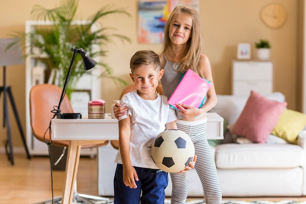 Irmã mais velha e irmão segurando cadernos e bola de futebol
