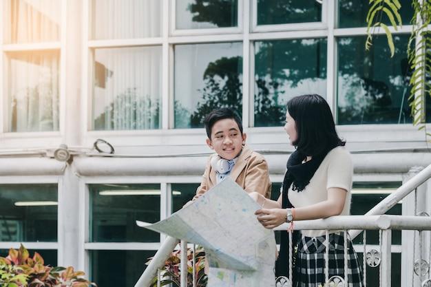 Irmã mais velha e turistas jovens irmão segurando e falando sobre o mapa na escada