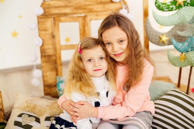 Irmã mais velha, irmã mais nova se abraçando, sentada no estúdio
