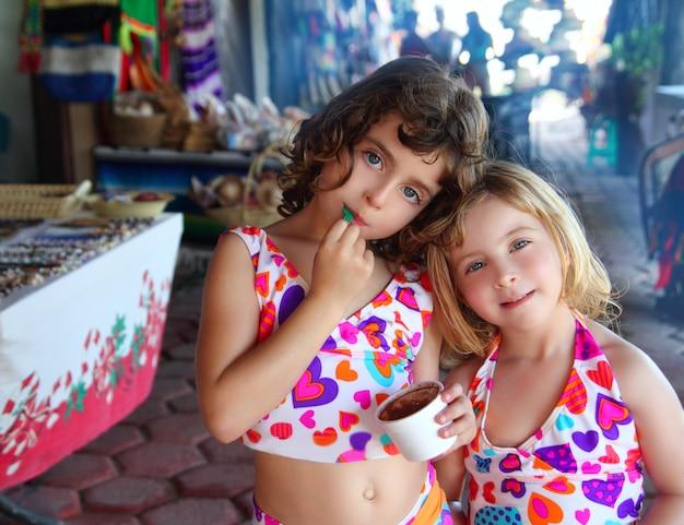 Irmã meninas comendo sorvete de chocolate verão
