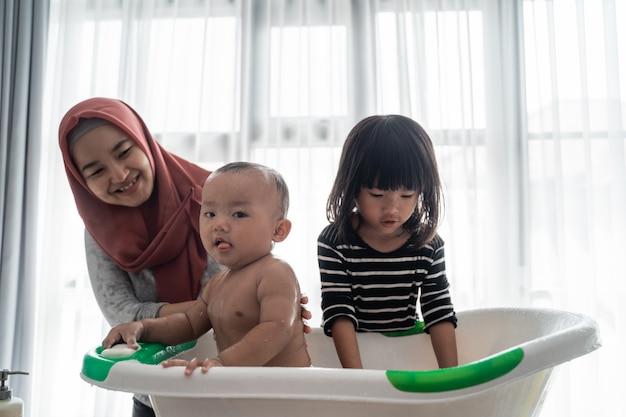 Irmã útil lavar seu irmão bebê durante a hora do banho