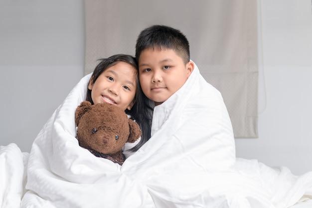 Irmão abraço irmã sob o cobertor