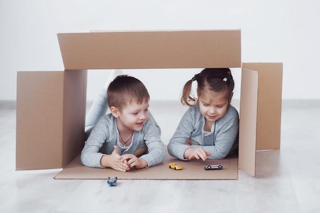 Irmão bebê e irmã criança brincando em caixas de papelão no berçário