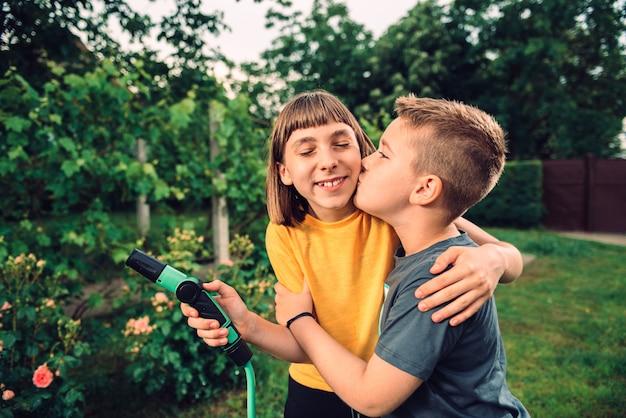 Irmão beijando e abraçando sua irmã ao ar livre