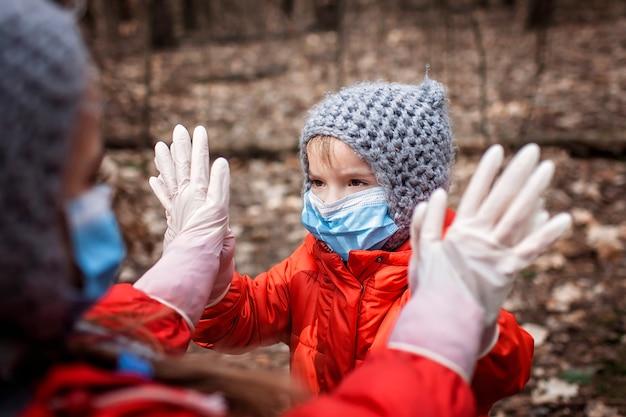 Irmão bonito em casacos vermelhos usando máscaras de respirador e luvas médicas jogando bolo patty
