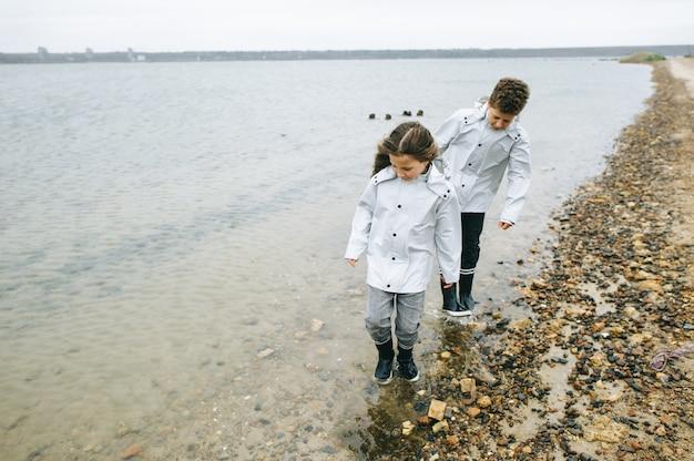Irmão com irmã se divertir no mar vestindo na capa de chuva