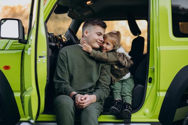 Irmão com irmãzinha sentada no carro verde