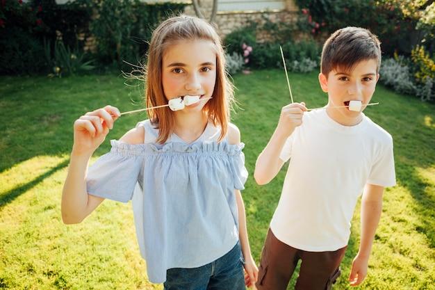 Irmão comendo marshmallow e olhando para a câmera