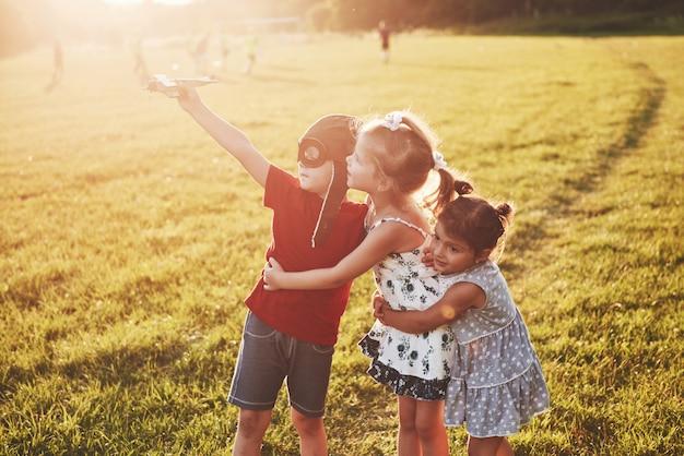 Irmão e duas irmãs estão brincando juntos. três crianças brincando com um avião de madeira ao ar livre