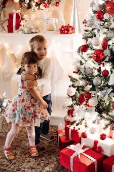 Irmão e irmã, abraçando perto de uma árvore de natal